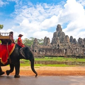 Man on elephant in front of Cambodia Siem Reap, included tours offered by Asia Vacation Group