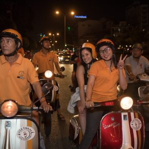 Customers on the back of a vespa with tour operators at night in Saigon, included in tours offered by Asia Vacation Group