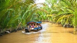 Tourists on boat cruising along Mekong River in Ben Tre, Vietnam, included in tours offered by Asia Vacation Group