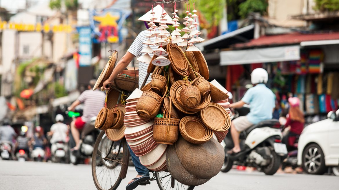 Hanoi Street vendor selling straw hat, included in tours offered by Asia Vacation Group