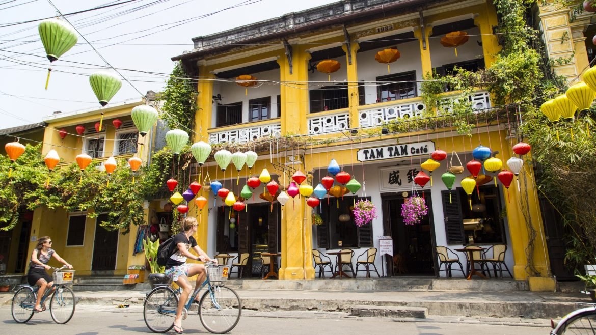 Hoi an Old town street with tourists on bicyles, included in tours offered by Asia Vacation Group