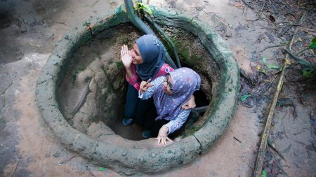 Two girls sneaking in Cu Chi Tunnels, Saigon, Vietnam, included in tours offered by Asia Vacation Group